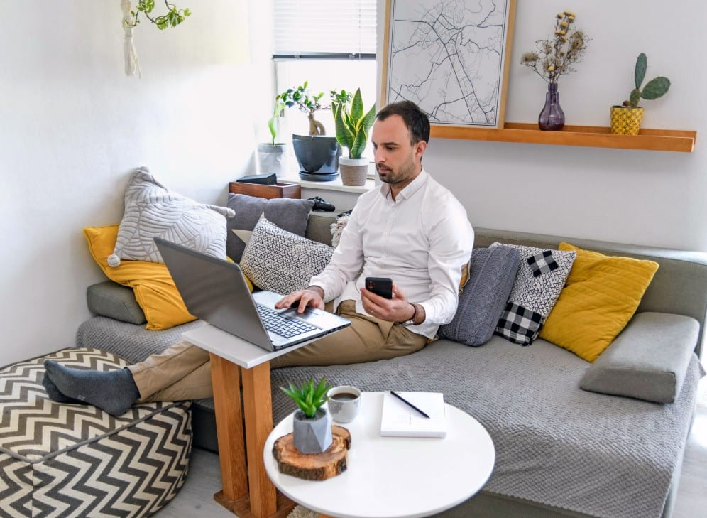 man-sitting-on-couch-in-living-room-working-on-laptop-computer-home-office-working-working-from-home_t20_G0re2E